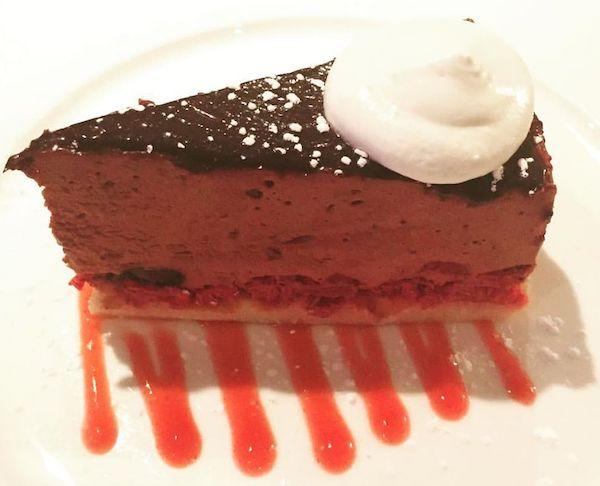 Chocolate mousse cake with whipped cream and raspberry sauce