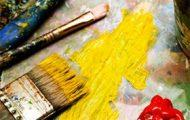 A paintbrush spreading yellow paint.